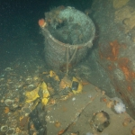 Water tight deck cannister with remains of a rubber life raft
